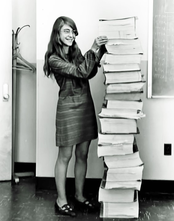 Margaret Hamilton standing beside the source code of the Apollo Guidance Computer. (Source: NASA)
